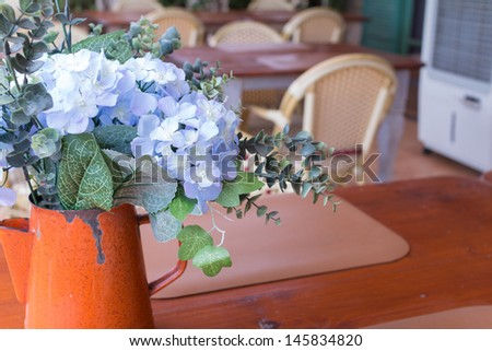 Little flowers decor in old pot on table