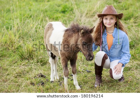 Little foal and girl - cute girl takes care of the pony foal - stock photo