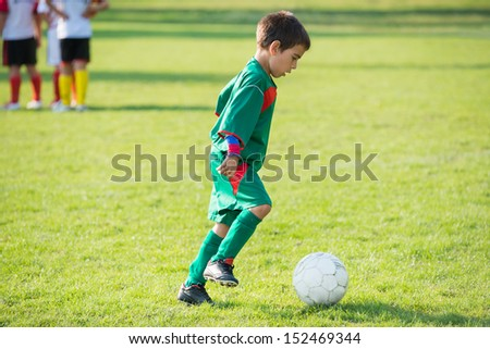 little football player kicking the ball - stock photo