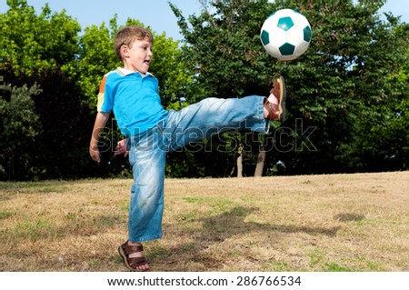 Little football player playing in the park with his father in football and hits the ball with all his strength  - stock photo