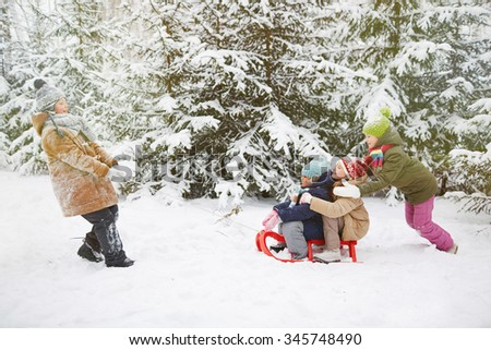 Little friends riding on sledge in winter park - stock photo