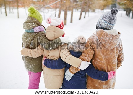 Little friends standing in embrace in winter forest - stock photo