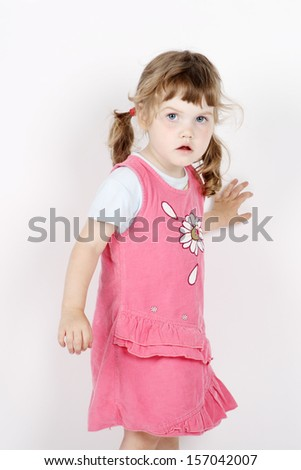 Little frightened girl stands and looks away on white background.