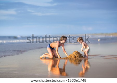 Little funny baby girl and her brother playing together on a beautiful beach at sunset, building sand castle next to the water - stock photo