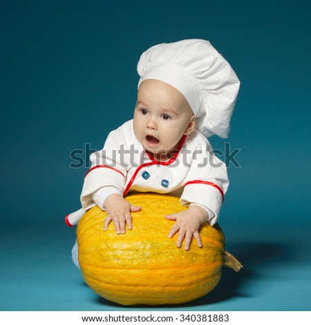 little funny baby with cook costume holds pumpkin