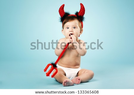 little funny baby with devil horns on blue background