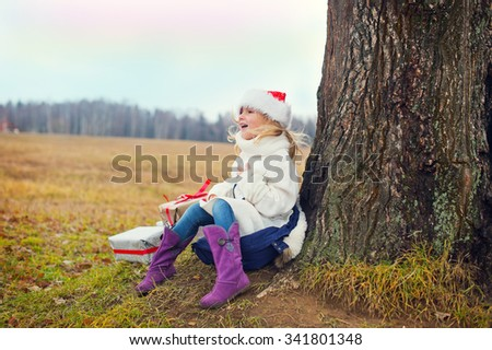 Little funny blond toddler girl in Santa hat sitting under huge tree in country side with gift boxes ready to celebrate New Year and Christmas