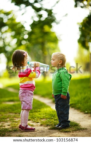 little funny boy and girl drinking mineral water in park - stock photo