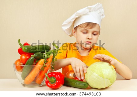 Little funny boy chooses vegetables for salad at the table