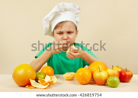 Little funny boy eat acidic orange at the table with fruits - stock photo