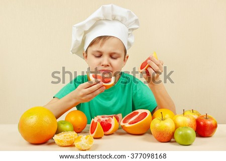 Little funny boy eat fresh grapefruit at the table with fruits