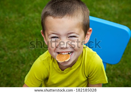 Little funny boy eating biscuit - stock photo