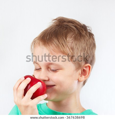 Little funny boy in a green shirt with juicy red apple - stock photo