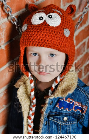Little funny boy in knitted handmade hippo hat - stock photo