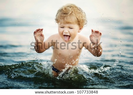 little funny boy playing in water - stock photo