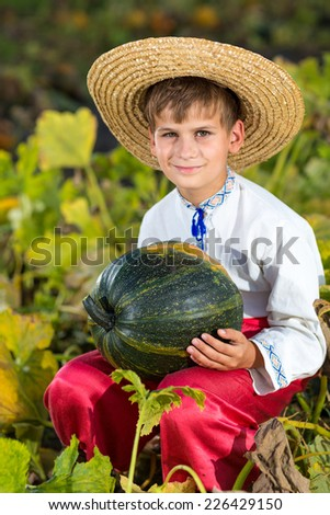 little funny boy with pumpkin in national Ukrainian clothes - stock photo