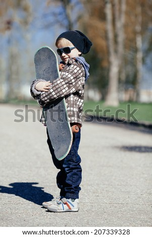 little funny boy with skateboard on the street - stock photo