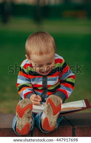 little funny boy writes with pen - stock photo