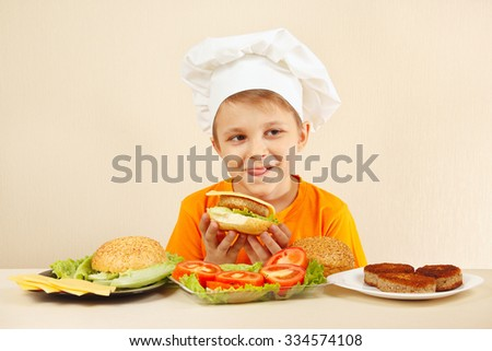 Little funny chef appetizing licked near the cooked hamburger - stock photo