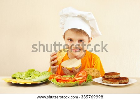 Little funny chef at the table with ingredients is going to cook a hamburger - stock photo