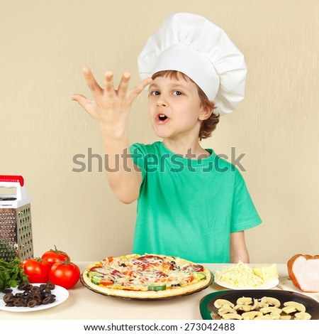 Little funny chef expressive enjoys a cooked pizza - stock photo
