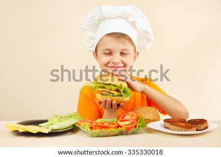 Little funny chef in chefs hat enjoys a cooking tasty hamburger - stock photo