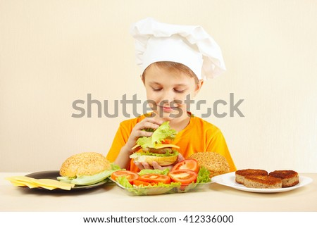 Little funny chef shows how to cook a hamburger - stock photo