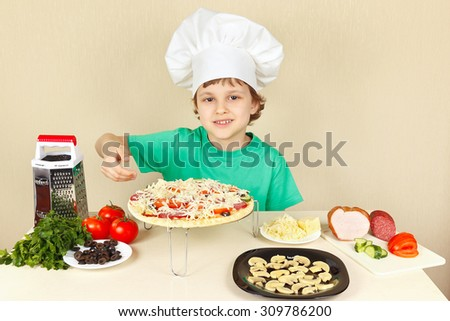 Little funny chef shows how to cook a pizza - stock photo