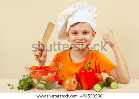 Little funny chef shows how to cook a vegetable salad