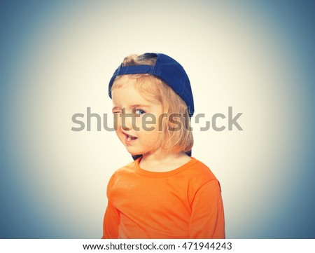 Little Funny girl in baseball cap and orange blouse. Isolated on  background