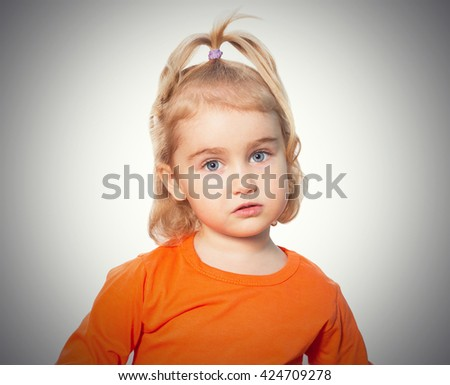 Little Funny girl in orange blouse. Isolated on gray background - stock photo