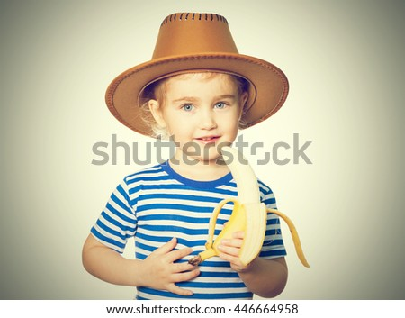 Little Funny girl in striped shirt and hat eats banana. Isolated on white background - stock photo