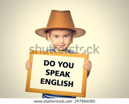 Little Funny girl in striped shirt with blackboard. Text do you speak english.  Isolated on gray background - stock photo