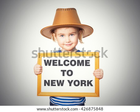 Little Funny girl in striped shirt with blackboard. Text welcome to New York. Isolated on a gray background. - stock photo