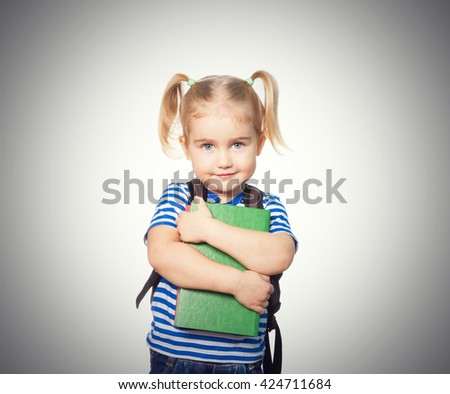 Little Funny girl in striped shirt with books. Isolated on gray background - stock photo