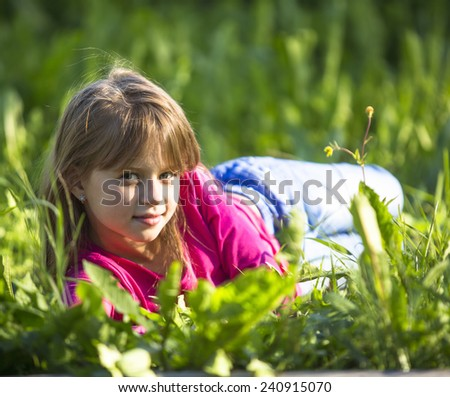 Little funny girl lying in the grass outdoors. - stock photo
