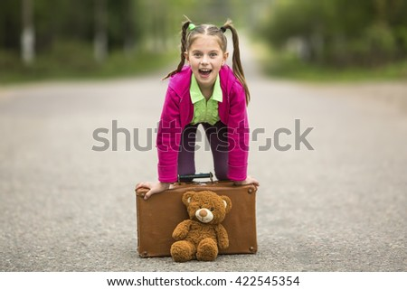 Little funny girl on the road with a suitcase and a Teddy bear. - stock photo