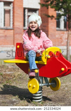 Little funny girl playing on the playground in the spring - stock photo
