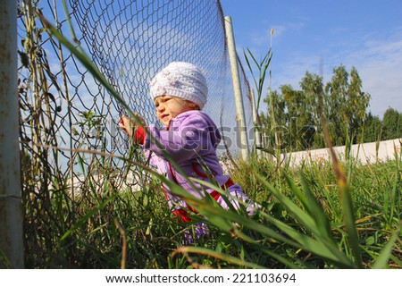 little funny girl with fence - stock photo