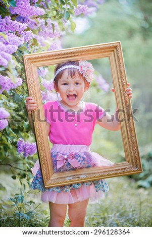 Little funny girl with old golden frame in hands standing in the lilac park on a sunny morning and smiling. - stock photo