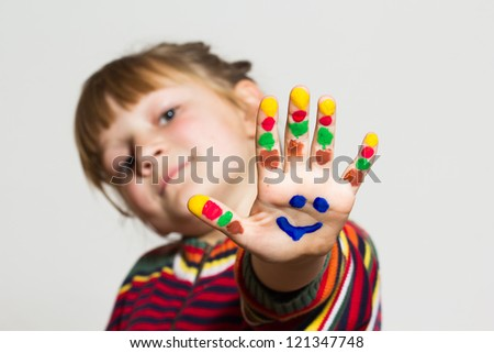 Little funny girl with painted hands - stock photo