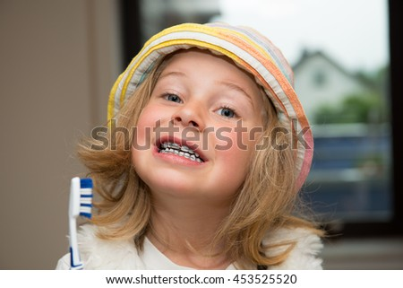 little funny girl with retainer and toothbrush looking in to the camera - stock photo