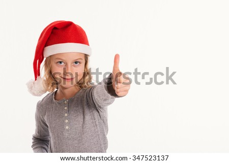 little funny girl with Santa- Claus cap and thumb up