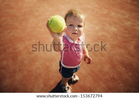 little funny girl with tennis ball - stock photo