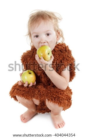 Little funny Neanderthal boy in a suit with dirty face eating an apple.  - stock photo