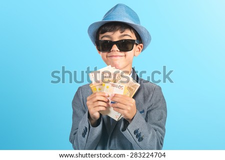 Little gangster holding a lot of money over colorful background - stock photo