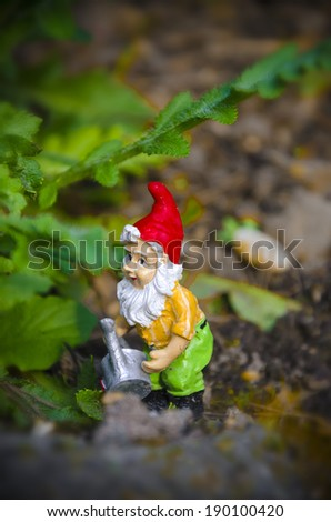Little garden gnome with watering can - stock photo