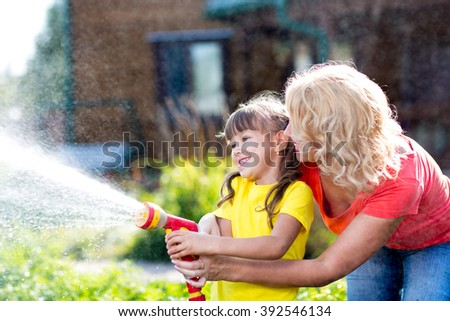 Little gardener child girl with mother watering on lawn near house - stock photo