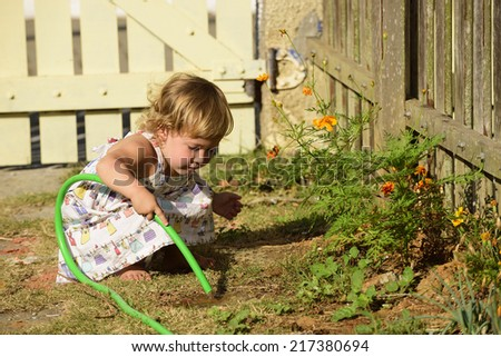 Little gardener: Cute girl watering flowers in the garden - stock photo