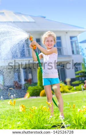 Little gardener girl watering flowers on the lawn near cottage. Vertical view - stock photo